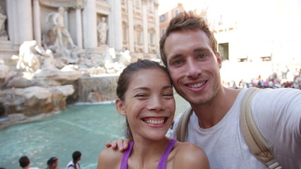Aufkleber - Tourist couple on travel taking selfie photo by Trevi Fountain in Rome, Italy. Happy young romantic couple traveling in Europe taking self-portrait with smartphone camera. Man and woman happy together