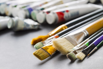Paint brushes on the background of tubes of paint