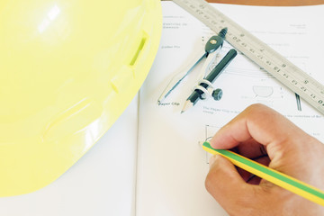hard hat with pencil compasses and rulers/book on table and wall