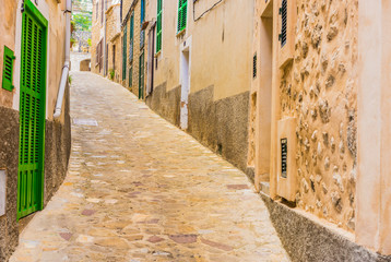 Fototapete - View of an mediterranean alleyway with rustic paving stones