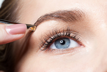 Closeup of a woman pulls out her eyebrows with tweezers