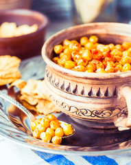 baked chickpeas with spices on rustic background, tone