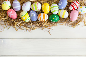 Colorful Easter Eggs in the nest of straw on the white wooden background