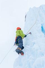 Alpinist man with  ice tools axe in orange helmet climbing a lar
