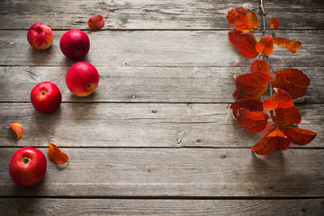 red apples and leaves on old wooden background