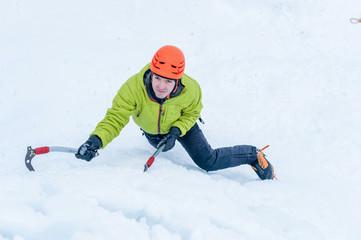 Ice climber man with  ice tools axe in orange helmet climbing a