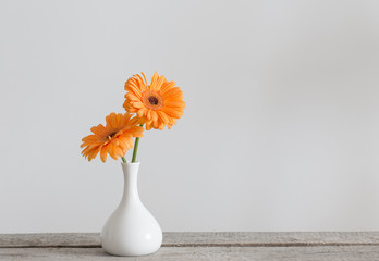Gerbera in vase on old wooden table