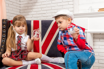 girl and boy sitting on chair with a British flag