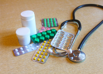 Different pills and stethoscope on the table