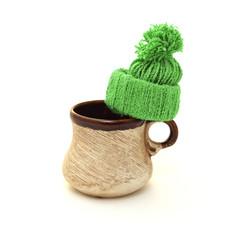 Коричневая керамическая чашка с шерстяной зеленой шапкой на белом фоне