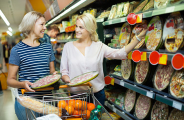 Adult girl helping mother in pizza section