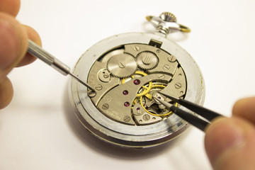hands repair an old watch
