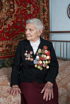 A female veteran of World War II, sitting in a cottage on the bed