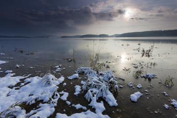 Sonnenaufgang am See mit Spiegelung schöner Wolken im Winter. Schnee in der Landschaft,Kälte in der Luft,die sich langsam mit der Sonne erwärmt