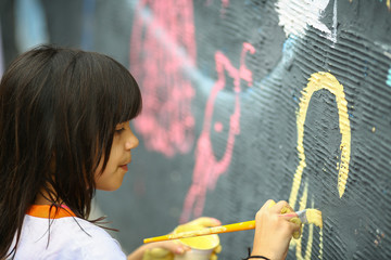 Young girl paints the  wall