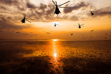 Silhouette of the military helicopter  moving into sky at sunset