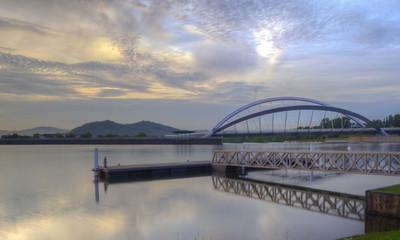 Putrajaya, Malaysia Bridge. A bridge and jetty over a dam in Putrajaya, Malaysia at sunrise.