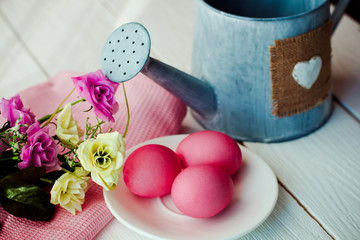 Easter pink Easter background with eggs and flowers on white wooden background