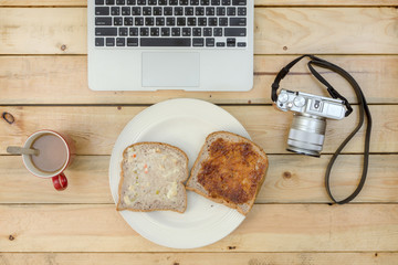 laptop, camera, coffee and  bread on wooden table.