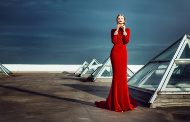 Gorgeous elegant woman in red long dress with diamonds on the roof