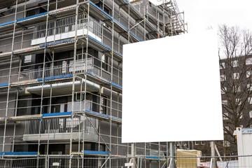 Leeres Schild vor Baustelle mit eingerüstetem Haus