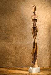 Woman wooden figurine on grunge background.