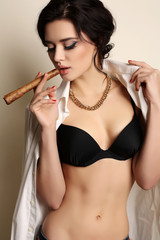 fashion studio photo of beautiful sensual girl with dark hair, in black lingerie and white shirt, smoking cigar