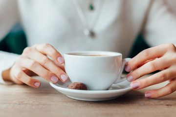 Woman holding a cup of coffee in closeup