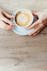 Female hands holding a cup of coffee
