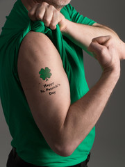 "Photograph of a man in a green T shirt pulling back his shirt sleeve to reveal a shamrock tattoo with a ""Happy St. Patrick's Day"" message."