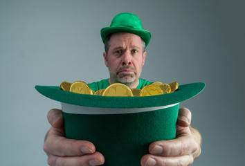 Photograph of a very sad Leprechuan holding out a green hat full of gold coins.