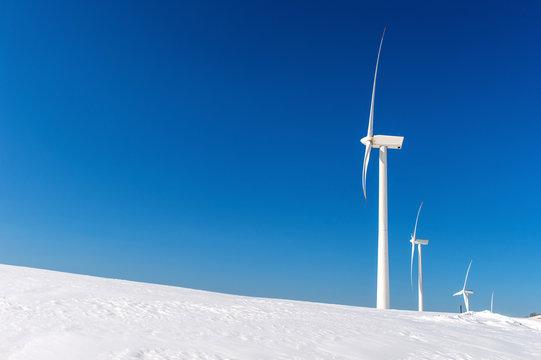 Wind turbine and blue sky in winter landscape.