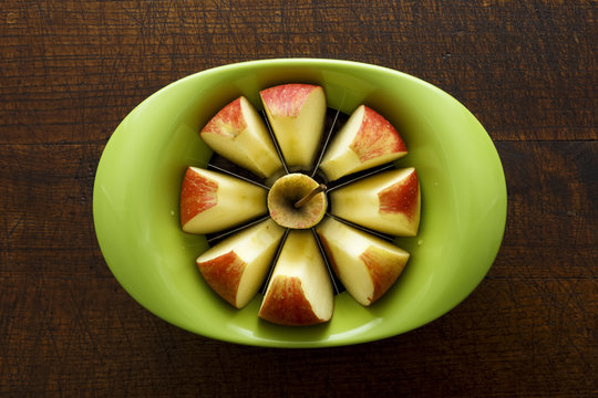 Green apple slicer with sliced apple segments from above, isolat