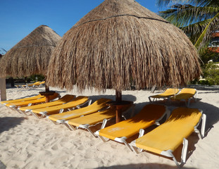 Straw umbrellas and folding chairs on a Caribbean beach in Riviera Maya, Mexico, for travel background