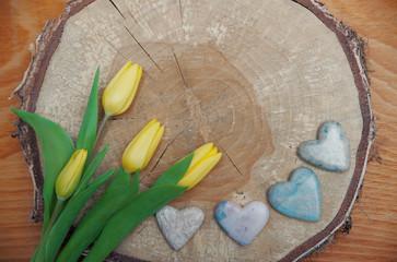 rustikales Holzscheibe mit gelben Tulpen und Speckstein-Herzen,