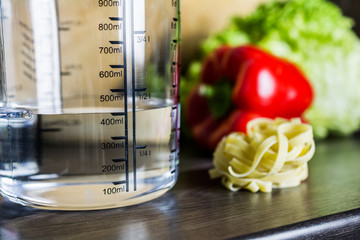 400ccm / 400ml Of Water In A Measuring Cup On A Kitchen Counter With Food