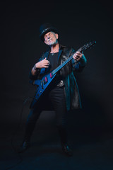 Senior heavy metal man with electric guitar against dark backgro