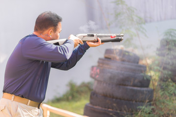 Man shooting shotgun , selective focus