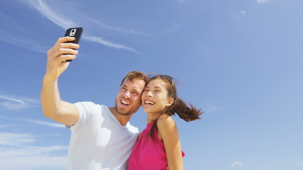 Aufkleber - People having fun. Couple taking smart phone selfie self-portrait photo pictures outside under the blue sky taking selfy photograph using smartphone camera. Young Asian woman, Caucasian man. RED EPIC.