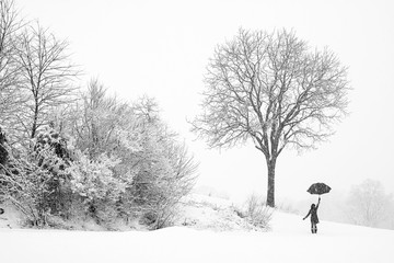Lonely  woman walking in snow storm