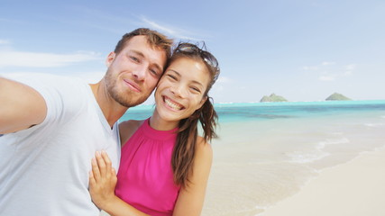 Aufkleber - Couple relaxing on beach taking selfie picture with camera smart phone. Young multiracial couple on getaway vacation in Hawaii having fun looking at camera. Candid closeup. RED EPIC SLOW MOTION.