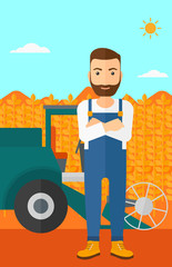Man standing with combine on background.