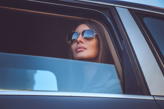 A woman in sunglasses looking through car's window.