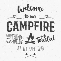 Vintage typography poster Illustration with sign welcome to campfire - Grunge effect. Funny lettering with symbols camp and trip, bonfire. On dark background for posters, camp clubs and Web emblems