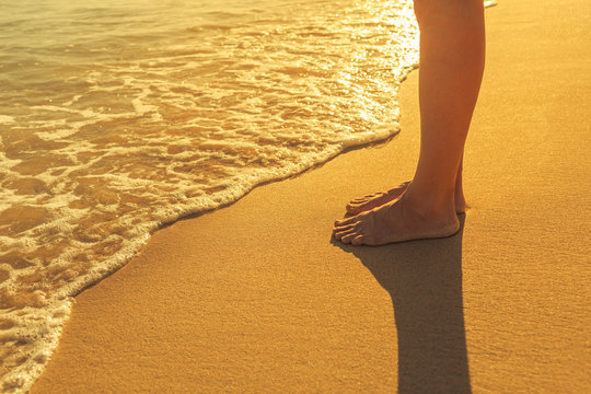 Woman standing on beach at sunset.