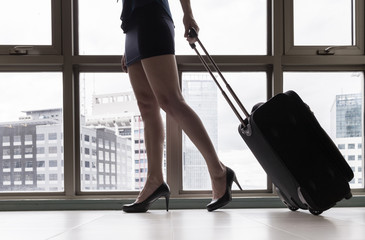 female walking with suitcase at airport.