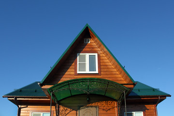 Green metal roof and attic window front view