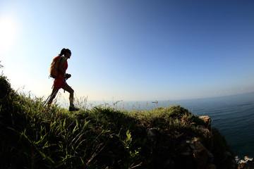 young woman hiker hiking on seaside mountain peak