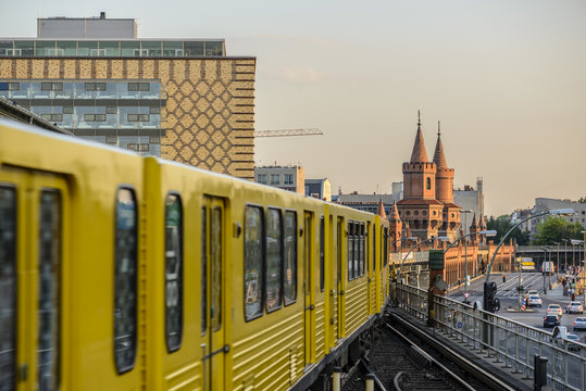 Yellow Subway train on trail to the historical bridge (Oberbaumbruecke) in Berlin, Germany, Europe
