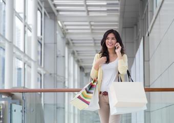 Happy young Asian woman shopping.